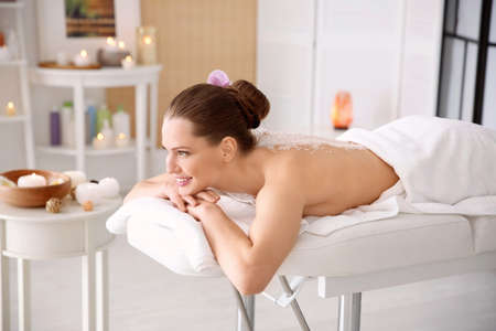 Photo pour Beautiful young woman having massage with body scrub in spa salon - image libre de droit