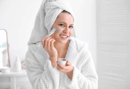 Photo pour Woman applying scrub onto face in bathroom - image libre de droit