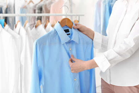 Photo pour Young woman holding hanger with shirt at dry-cleaner's - image libre de droit
