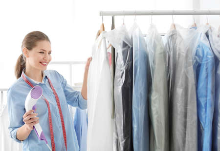 Foto de Young woman steaming shirt at dry-cleaner's - Imagen libre de derechos