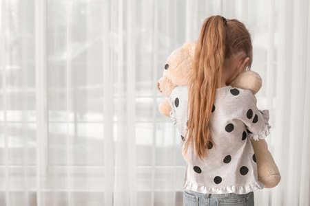 Foto de Lonely little girl with toy indoors. Autism concept - Imagen libre de derechos