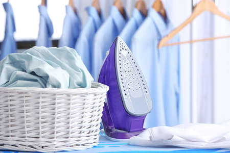 Photo pour Wicker basket with clothes on ironing board at dry-cleaner's - image libre de droit