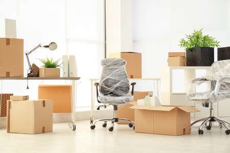 Foto de Moving boxes and furniture in new office - Imagen libre de derechos