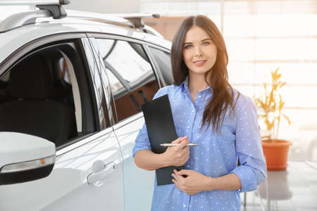 Photo for Saleswoman with clipboard in salon. Buying new car - Royalty Free Image
