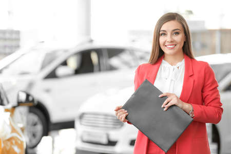 Photo for Young woman with clipboard in car salon - Royalty Free Image