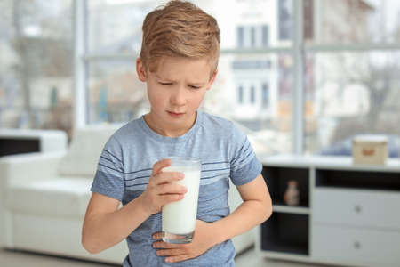Photo for Little boy with dairy allergy holding glass of milk indoors - Royalty Free Image