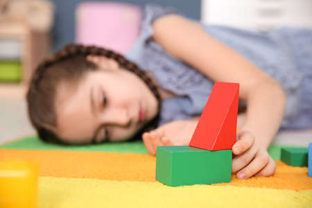 Foto de Little girl with autistic disorder playing at home, closeup of cubes - Imagen libre de derechos