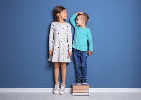 Foto de Little girl and boy measuring their height near color wall - Imagen libre de derechos
