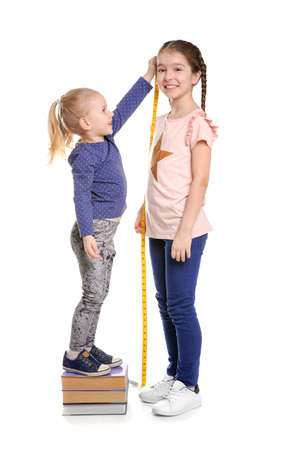 Foto per Little girls measuring their height on white background - Immagine Royalty Free