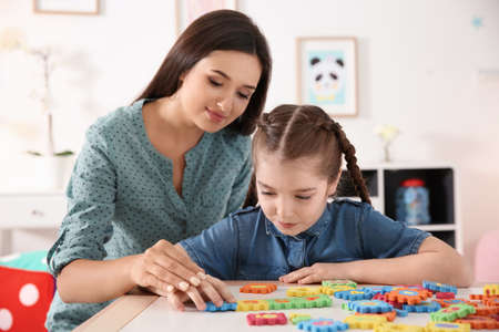 Foto de Young woman and little girl with autistic disorder playing at home - Imagen libre de derechos