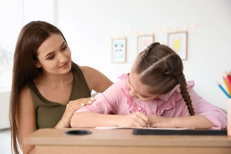 Foto de Young woman and little girl with autistic disorder drawing at home - Imagen libre de derechos