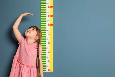 Photo pour Little girl measuring her height on color background - image libre de droit