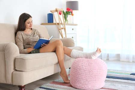 Photo for Young woman with broken leg in cast reading book while sitting on sofa at home - Royalty Free Image