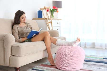 Foto de Young woman with broken leg in cast reading book while sitting on sofa at home - Imagen libre de derechos