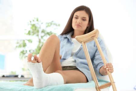 Foto de Woman with broken leg in cast on couch - Imagen libre de derechos