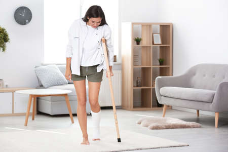 Photo pour Young woman with crutch and broken leg in cast at home - image libre de droit