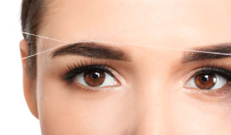 Foto de Young woman correcting eyebrow shape with thread, closeup - Imagen libre de derechos