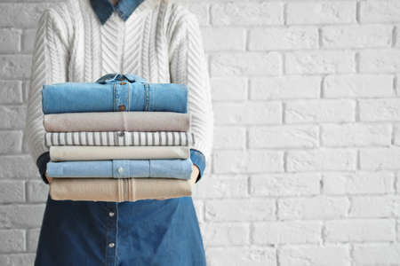 Photo pour Woman holding stack of clean clothes near brick wall - image libre de droit