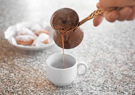 Foto de Woman pouring aromatic coffee into cup on table - Imagen libre de derechos