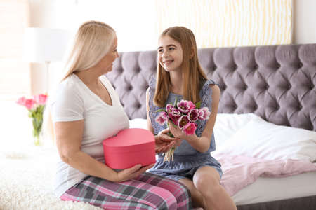 Photo for Happy mature woman receiving bouquet and gift from her teenage granddaughter at home - Royalty Free Image