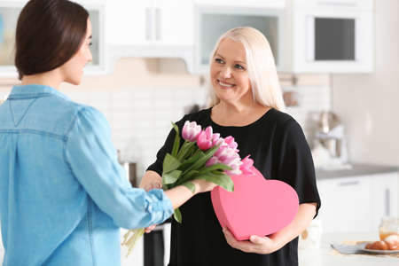 Photo for Daughter congratulating happy mature woman on Mother's Day at home - Royalty Free Image
