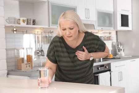 Photo pour Mature woman having heart attack in kitchen - image libre de droit