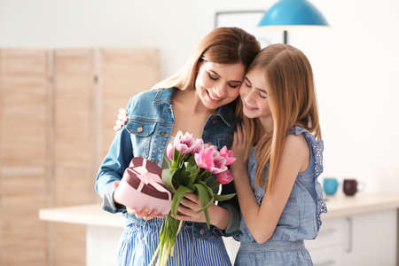Photo for Teenage daughter congratulating happy woman on Mother's Day at home - Royalty Free Image