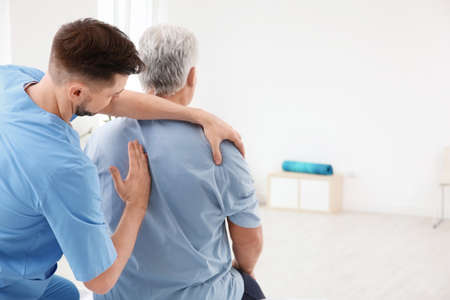 Photo for Young physiotherapist working with senior patient in clinic - Royalty Free Image