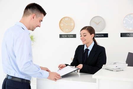 Photo pour Young man filling form at reception desk in hotel - image libre de droit