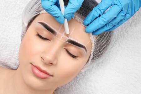 Photo pour Cosmetologist preparing young woman for eyebrow permanent makeup procedure, closeup - image libre de droit