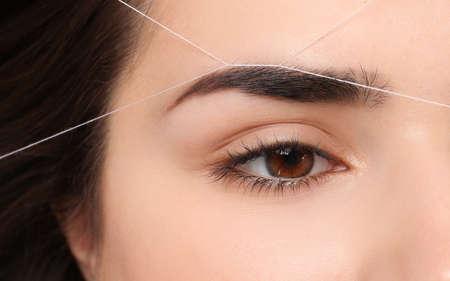 Photo pour Young woman having professional eyebrow correction procedure, closeup - image libre de droit