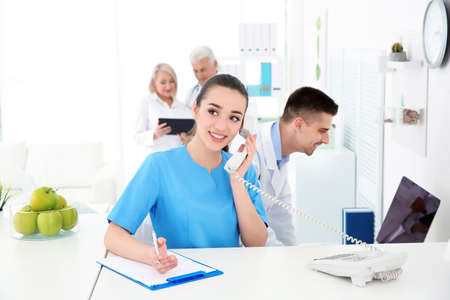 Photo for Young female receptionist working in hospital - Royalty Free Image