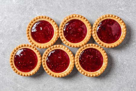 Foto de Tasty tartlets with jam on grey background - Imagen libre de derechos