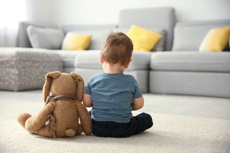 Photo pour Little boy with toy sitting on floor in living room. Autism concept - image libre de droit