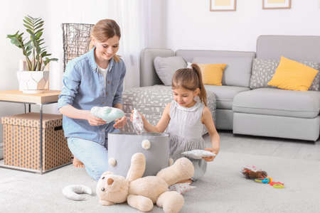 Photo pour Housewife and daughter picking up toys after playing at home - image libre de droit