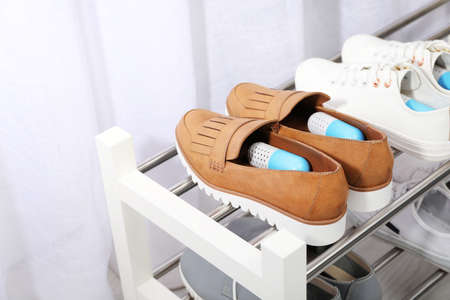 Foto für Shoes with capsule fresheners on rack in room - Lizenzfreies Bild