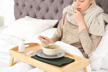 Foto de Sick young woman eating broth to cure cold in bed at home - Imagen libre de derechos