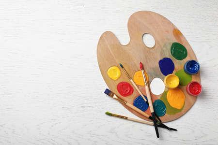 Foto de Wooden palette with colorful paints and brushes on light background, top view - Imagen libre de derechos
