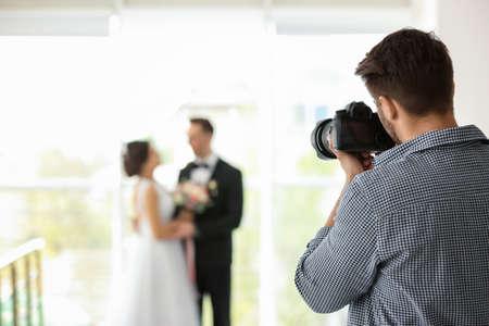 Photo pour Professional photographer taking photo of wedding couple in studio - image libre de droit