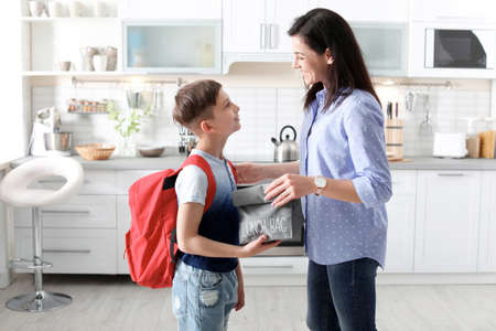 Photo pour Young woman helping her little child get ready for school at home - image libre de droit