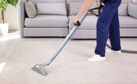 Photo for Male worker removing dirt from carpet with professional vacuum cleaner indoors - Royalty Free Image