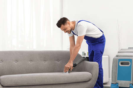 Photo pour Dry cleaning worker removing dirt from sofa indoors - image libre de droit