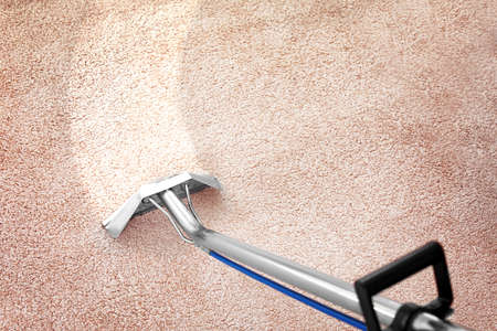Foto de Removing dirt from carpet with professional vacuum cleaner indoors - Imagen libre de derechos