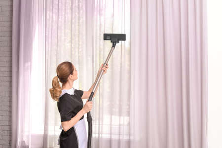 Photo pour Female worker removing dust from curtains with professional vacuum cleaner indoors - image libre de droit