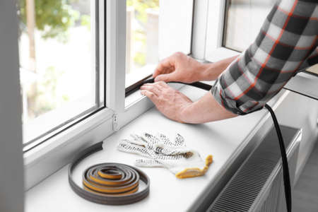 Photo for Young man putting sealing foam tape on window indoors - Royalty Free Image