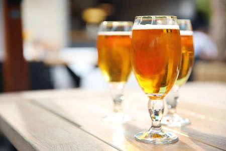 Foto de Glasses with cold beer on table against blurred background - Imagen libre de derechos