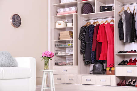 Photo pour Modern wardrobe with stylish clothes in room interior - image libre de droit