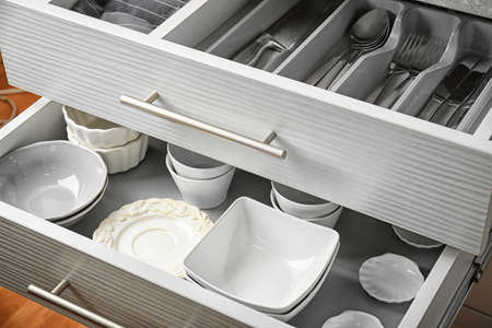 Photo for Ceramic dishware and cutlery in kitchen drawers - Royalty Free Image