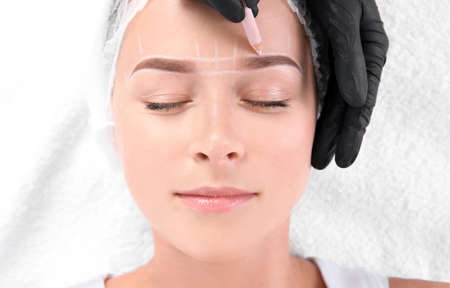 Photo pour Young woman undergoing eyebrow correction procedure in salon, top view - image libre de droit