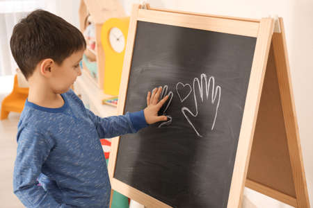 Foto de Little boy putting his palm on drawing at child psychologist's office. Autism concept - Imagen libre de derechos